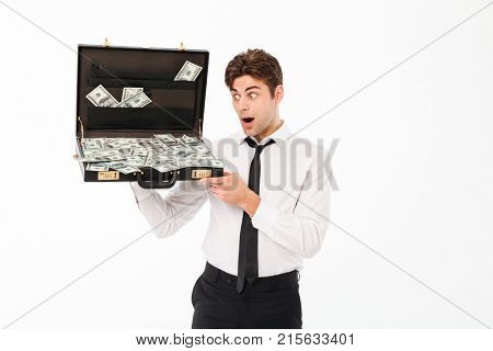 Portrait of a shocked young businessman dressed in white shirt holding briefcase full of money banknotes isolated over white background