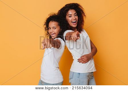 Portrait of two smiling african sisters standing back to back and pointing finger at camera isolated over orange background