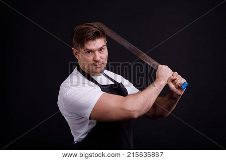 A man on a black background with a machete in his hands, swinging, dressed in a white T-shirt, and a black apron, looks into the camera.