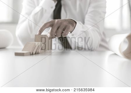 Man Preventing Dominoes From Crumbling On A White Office Table