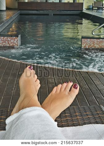 Do more of what makes you happy make time for yourself. Woman feet beside spa swimming pool.