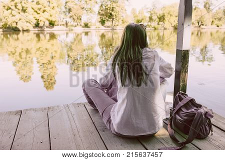BUCHAREST ROMANIA - AUGUST 29 2014: Girl with melancholic mood alone with her thoughts in silence on lakeside in Herastrau Park in Bucharest.