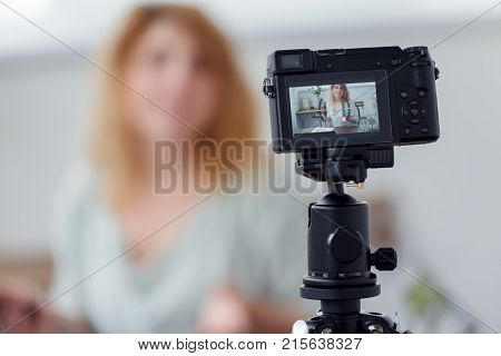 Blurred image of woman blogger at table with florarium. Shooting master class on video camera