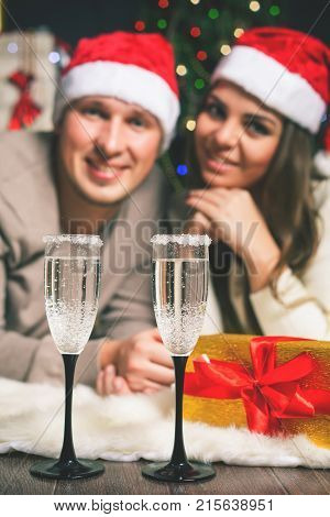 Cristmas couple young man and girl near the decorated Christmas tree celebrating New Year. Clink glasses. Christmas party, drinking champagne. Twelve o'clock, midnight