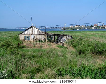 Single hut on the seashore among the reeds on a clear sunny day. Greenery blue sky sea bay shack and the city on the other shore on the horizon