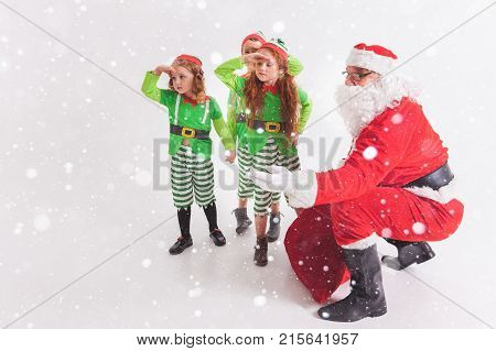 Santa's helpers are working at North Pole, elves and kids holding gift boxes. Merry Christmas. Santa sitting at many gift boxes and reading wishes list. Letters To Santa Claus. Wish list poster
