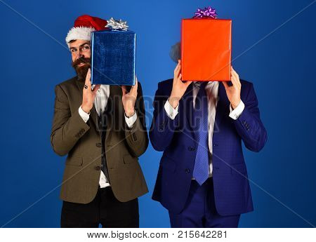 Businessmen Hide Faces Behind Red And Blue Present Boxes.