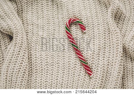 Stylish Christmas Flat Lay. Peppermint Candy Cane On Rustic Knitted Sweater Background Top View. Spa