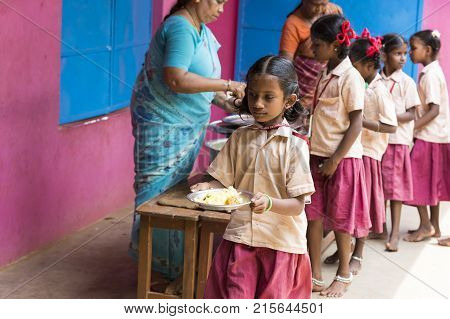PONDICHERY PUDUCHERY INDIA - SEPTEMBER 04 2017. Unidentified boys girls children get in lines with their plates to be served of rice and eggs at the outdoor canteen of the school.
