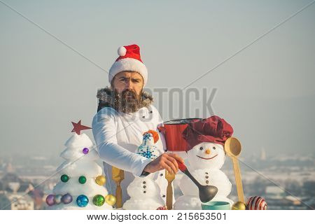 Christmas and new year holidays food. Unhappy hipster with ladle in white uniform. Cook snowmen and snow xmas tree on blue sky. Cooking and diet concept. Man in santa hat ladling soup on winter day.