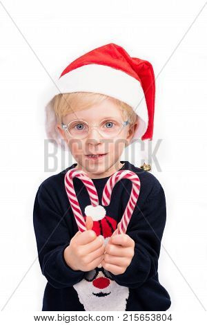 Love Christmas: A cute 4 year old boy wearing glasses is holding two candy sticks, forming a heart shape on a perfect white studio background.