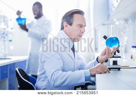 Chemical lab. Serious handsome smart scientist holding a flask and looking at the blue liquid in it while working in the chemical lab