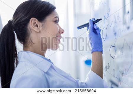 Female researcher. Happy positive young woman standing in front of the whiteboard and writing on it while doing a research