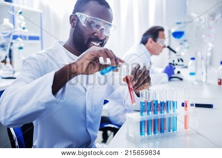 Medical testing. Delighted nice professional scientist holding test tubes and working with them while doing medical testing