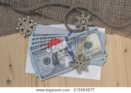 Benjamin Franklin in a Santa Claus hat on a bill and background in retro style. Christmas decorations