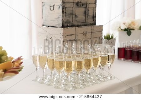 Welcome drinks stand with a lot of champagne glasses, fruits and juices on wedding and retro suitcase behind