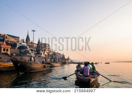 VARANASI INDIA - MARCH 15 2016: Wide angle picture of people on the boat looking the riverbank in front of Manikarnika Ghat in Ganges River during sunrise in Varanasi India.