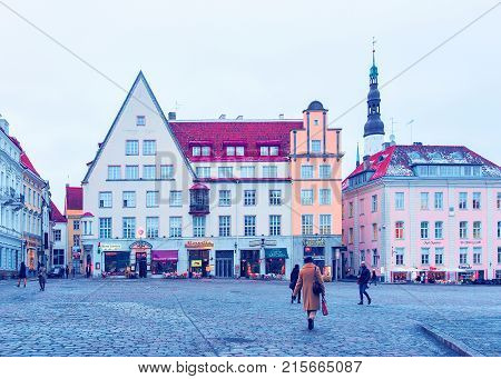 Tallinn Estonia - February 27 2017: People on Town Hall Square in the Old city of Tallinn Estonia in winter. Church of Holy Spirit on the background