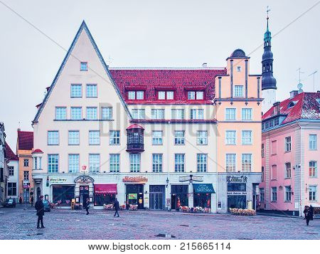 Tallinn Estonia - February 27 2017: People on Town Hall Square in the Old city Tallinn Estonia in winter. Church of Holy Spirit on the background