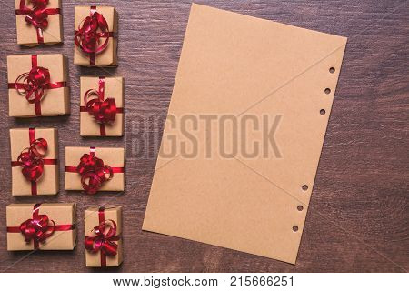 gifts wrapped in kraft paper and red ribbon and bow, paper for empty space for text on a wooden background. View from above, flat lay design.