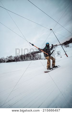 Snowboarder In A Black Helmet Riding On A Snowy Track.