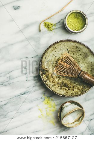 Flat-lay of Japanese tools and bowls for brewing matcha green tea. Matcha powder in tin can, Chashaku spoon, Chasen bamboo whisk, Chawan bowl, cups over grey marble background, top view, copy space