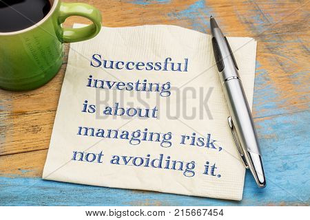 Successful investing is about managing risk, not avoiding it - handwriting on a napkin with a cup of coffee