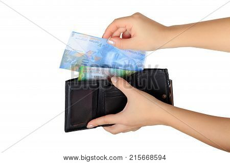 the woman pulls out a Swiss francs from her purse isolated on white background