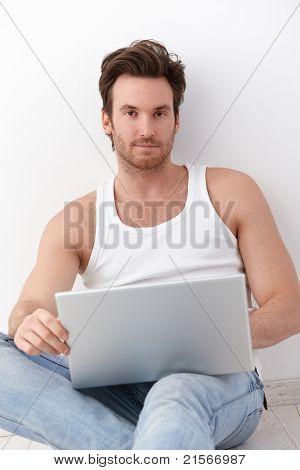 gutaussehend junger Mann mit Laptop, sitzen auf Boden.?