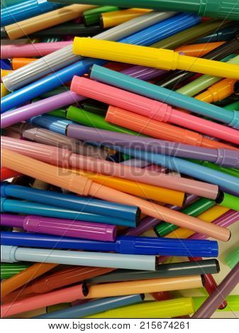 stacked, untidy markers of various colors, background