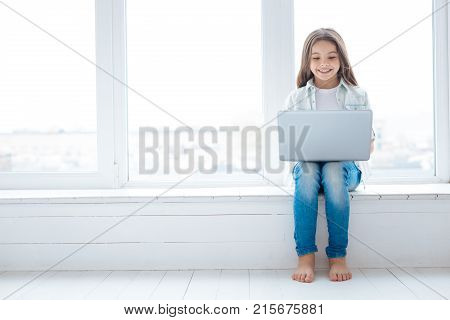Funny picture. Charming beautiful young girl holding laptop on her knees while sitting on the window sill and looking at the screen