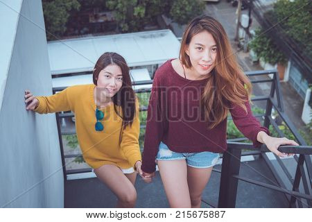 Lesbian Couple Together Concept. Couple Of Young Asian Women Walking Up The Stairs To Top Roof.