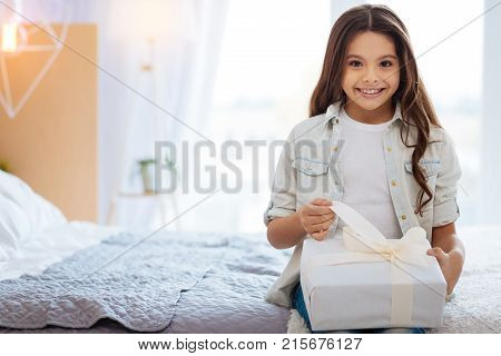 Surprise me. Nice optimistic genuine girl  open her surprise and sitting on the bed edge while looking straight