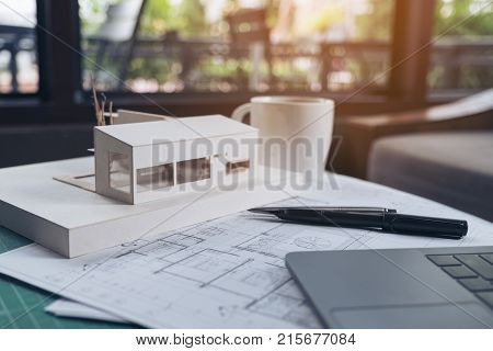 An architects designed architecture model with shop drawing paper and laptop on table