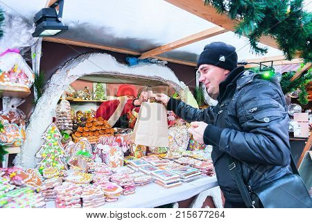 Riga Latvia - December 28 2016: Man at the stall on Christmas Market at Dome Square in Riga Old Town in winter