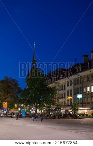 Bern Switzerland - August 21 2013: People on Marktgasse street in old city center of Bern Switzerland. Illuminated late in the evening