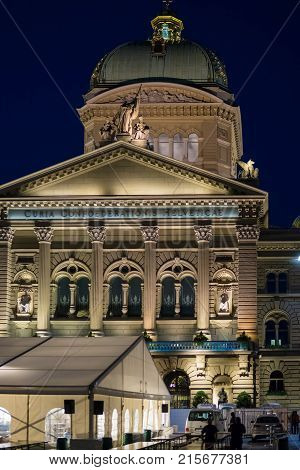 Bern Switzerland - August 21 2013: Facade of Federal Palace of Switzerland in Bern Switzerland. Illuminated late in the evening. People on the background