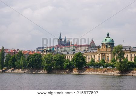 Vltava River embankment with Prague Old Town Czech Republic. Strakova Academy and Saint Vitus Church on the background