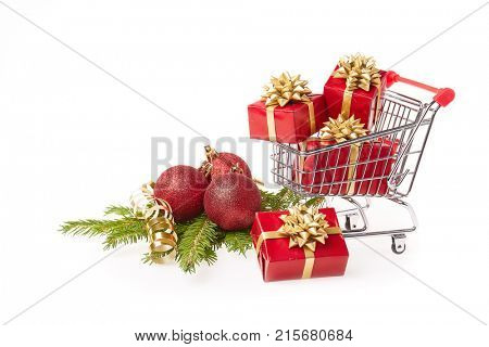 Shopping trolley with red gift boxes and brenches of fir-tree with decoration on a white background. Christmas and New Year sale.