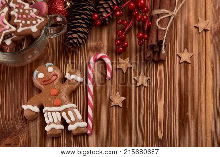 Christmas decor with homemade gingerbreads on a wooden background with copy space for text. Top view. For greeting card.