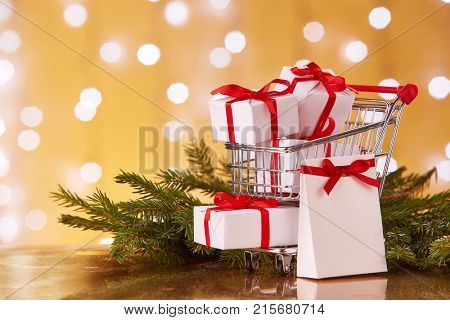 Shopping trolley with white gift boxes and brenches of fir-tree with decoration on a yellow background with light of garland. Christmas and New Year sale.