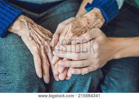 Hands Of An Old Woman And A Young Man. Caring For The Elderly. Close Up