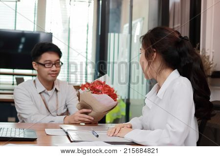 Attractive young Asian woman accepting a bouquet of red roses from boyfriend in office on valentine's day. Love and romance in workplace concept. Selective focus and shallow depth of field.