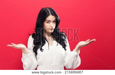 Young woman shrugging on a solid background