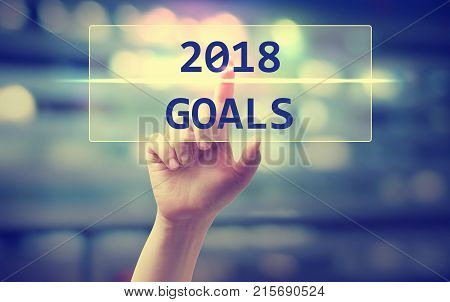 2018 Goals concept with hand pressing a button on blurred abstract background