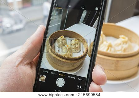 Shanghai, China - Nov 7, 2017: Taking photo of Shanghai dumpling, also called xiaolongbao with a smartphone. Xiaolongbao is a type of popular traditional food in China.