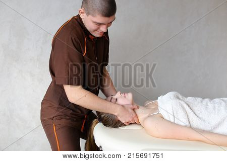 Experienced doctor professionally kneads neck and conducts therapeutic procedure for neck, removes discomfort of young woman who lies on couch, covered with terry towel. Man of European appearance with short haircut dressed in brown medical uniform from s poster