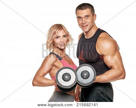 Portrait of healthy fitness man and woman posing with dumbbells