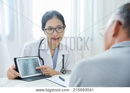 Young Asian Female Doctor wear glasses smiling and discussing with senior man patient about a chest radiograph in digital tablet computer in medical office. X-ray.