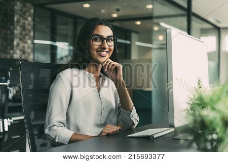 Portrait of cheerful young Latin-American businesswoman wearing glasses sitting at her workplace with computer in office looking at camera with hand on chin and smiling